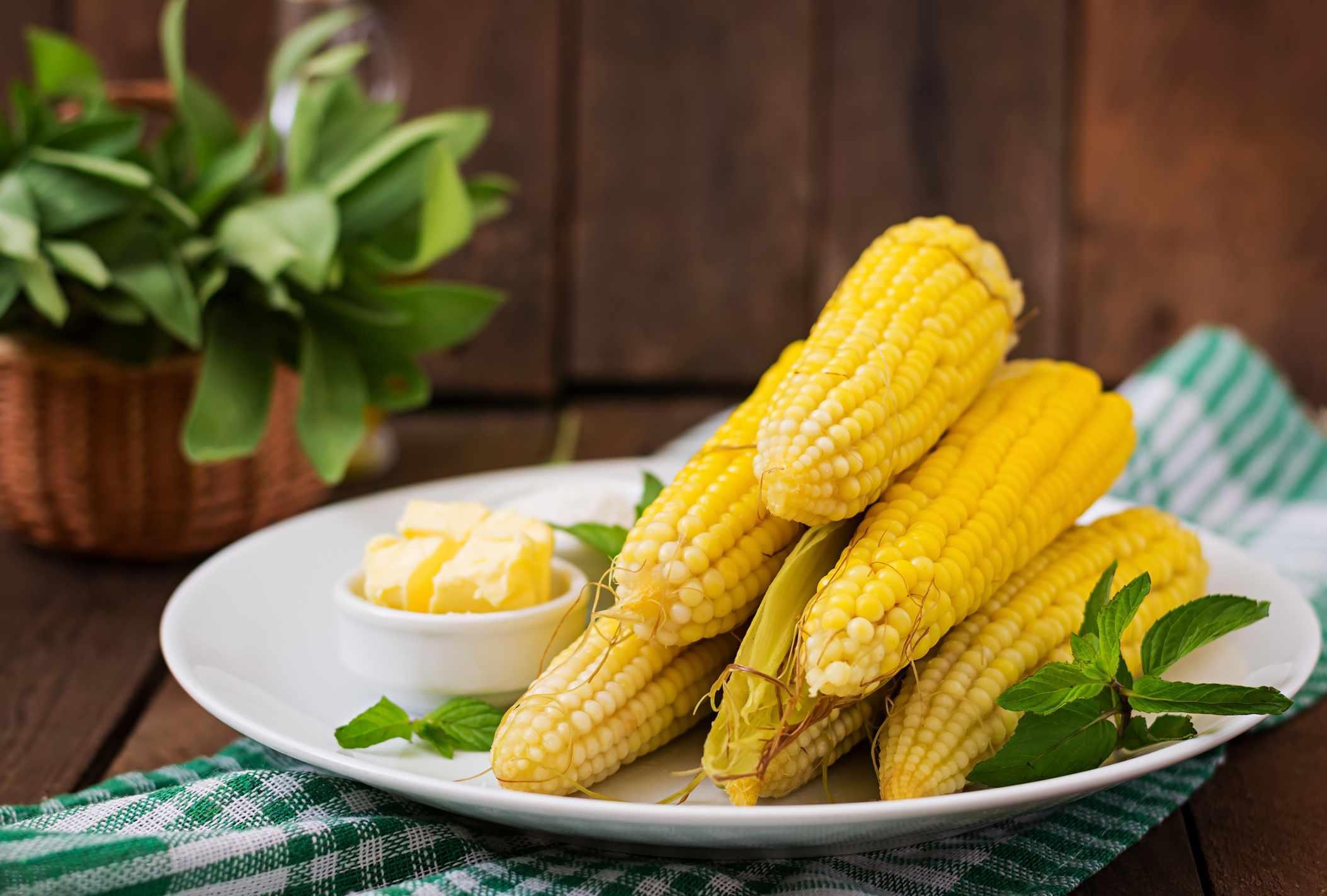 seis mazorcas de maíz cocidas y peladas en un plato con un pequeño tazón de mantequilla al lado
