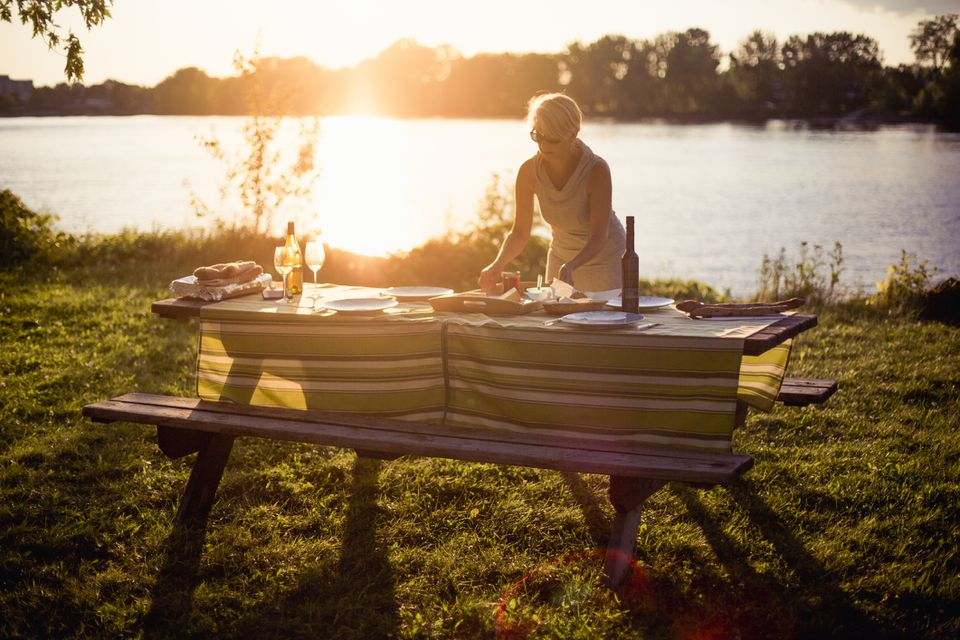 Woman arranging food on picnic table at lakeshore during sunny day Canada, Quebec, Montreal
