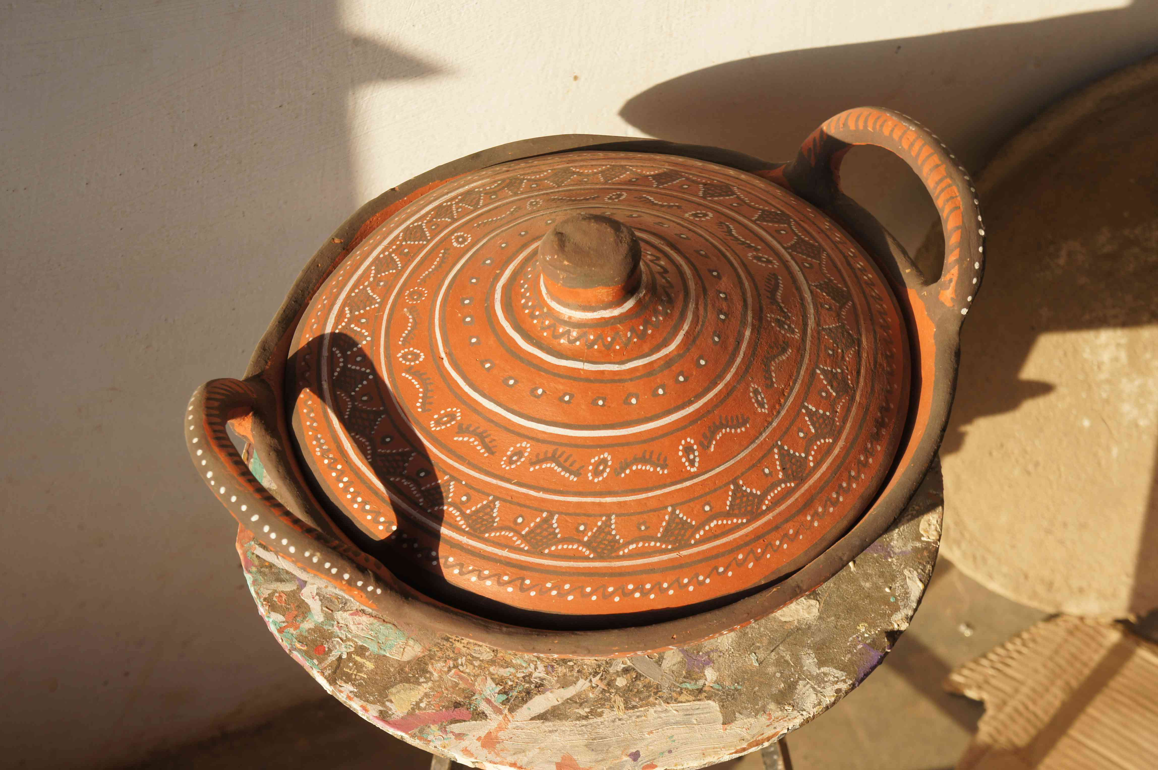 a terracotta dish and lid on a stool. The dish is decorated with blakck and white paint