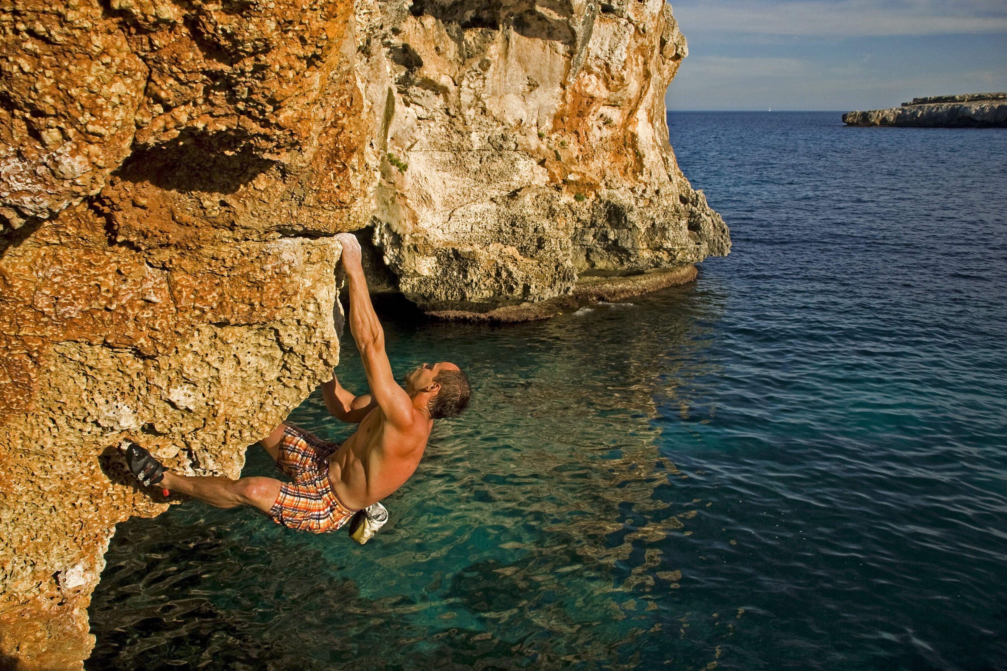 A deep water soloist cracks clean rock above the Mediterranean Sea on the coast of Mallorca.