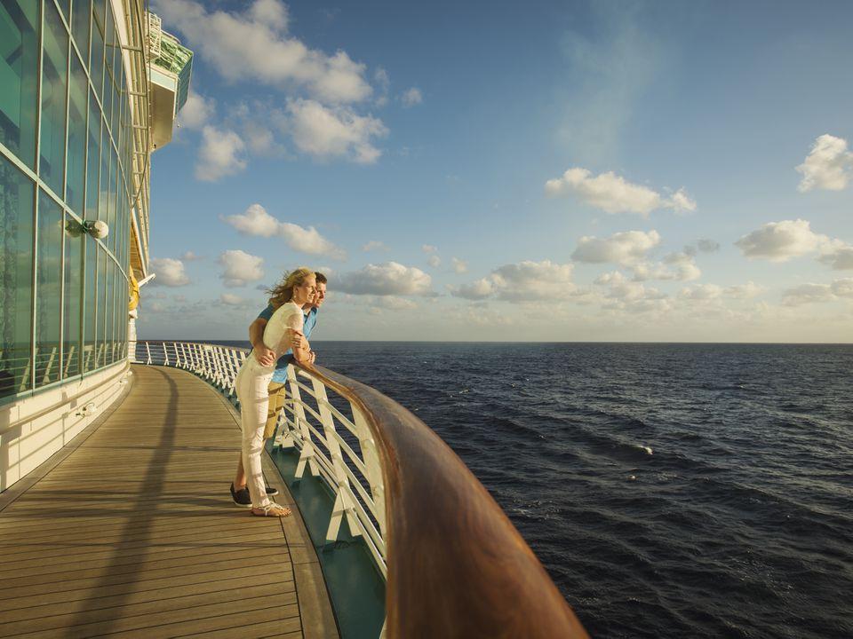 Pareja caucásica admirando la vista desde la cubierta del crucero