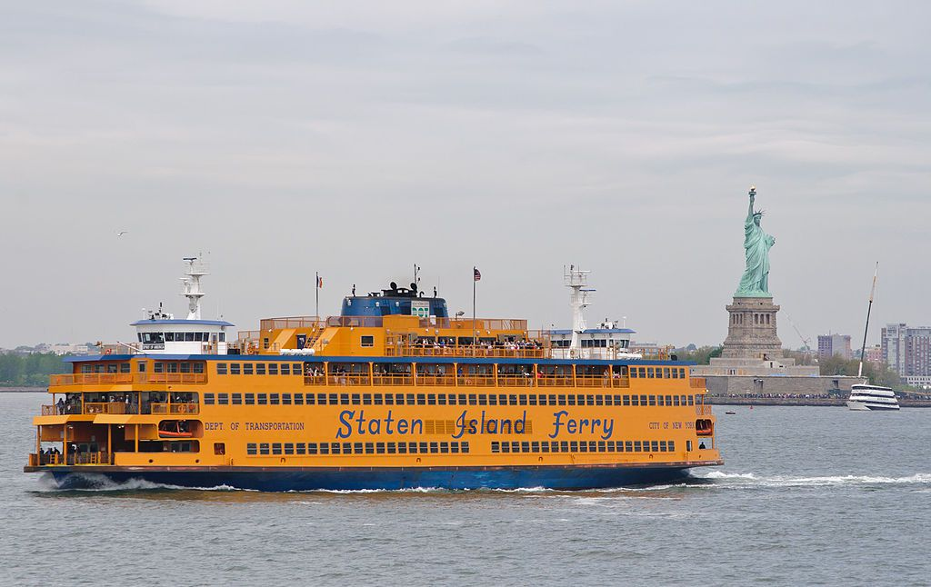 The Staten Island Ferry, which takes 25 minutes one way to travel between Battery Park in Manhattan and St. George on Staten Island, is probably the greatest bargain in New York City, as it offers some of the best views of the harbor and the world-famous skyline, for free. Each of the distinctive double-ended ferries carries a name. This particular one, heading for Staten Island, is named Spirit of America. I am heading for Manhattan on the John F. Kennedy. In the background, there are a few cranes around the Statue of Liberty; due to security upgrades and renovations, the Statue has been closed since October 2011, and will remain closed through summer 2012.