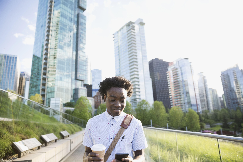 Hombre de negocios con café usando un teléfono celular en una ciudad debajo de edificios de gran altura