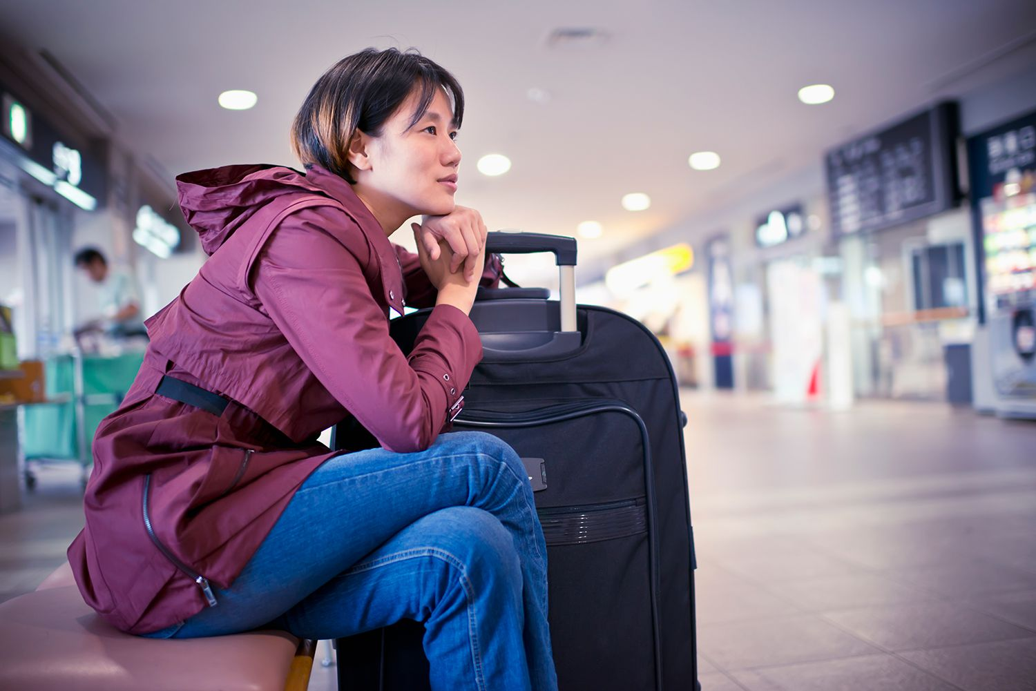 Young woman leaning against on big baggage