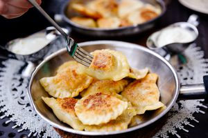Eating traditional Polish dumplings Pierogi with fork