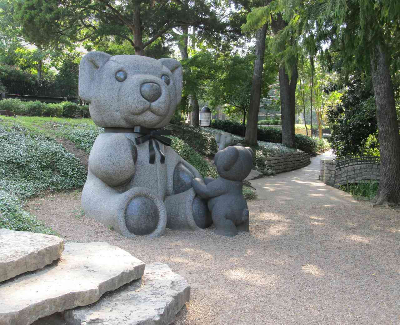 Sitting teddy bear sculpture with a smaller bear standing by the bigger bear's foot