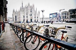 Parked bicycles with Duomo of Milan in background