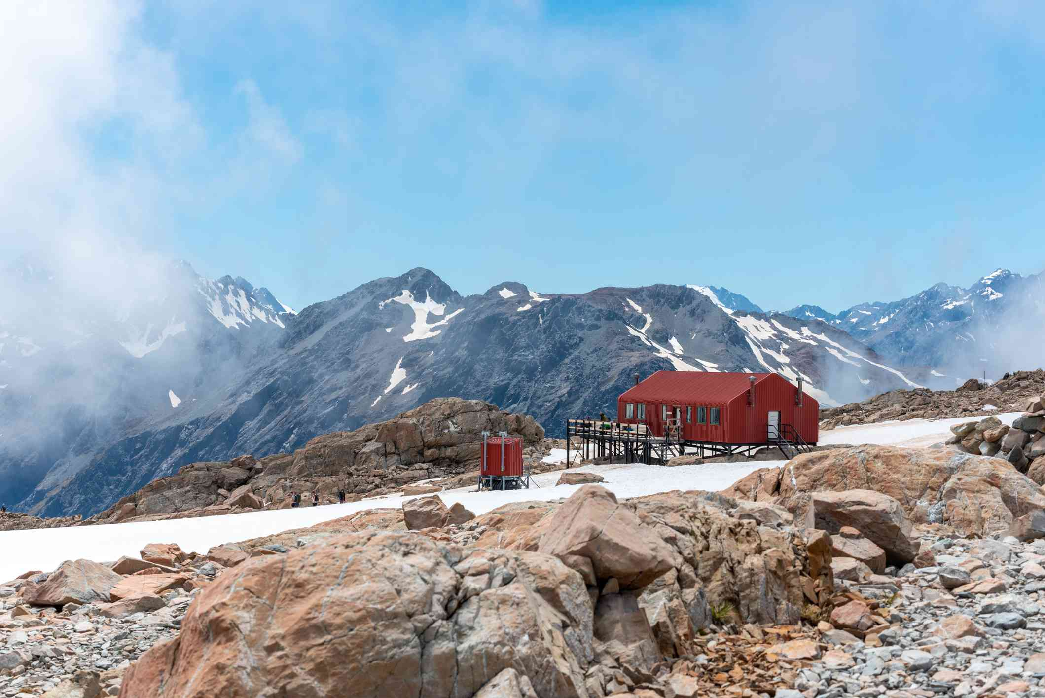 red hut in mid-ground with rocks covered in snow and mountains and clouds