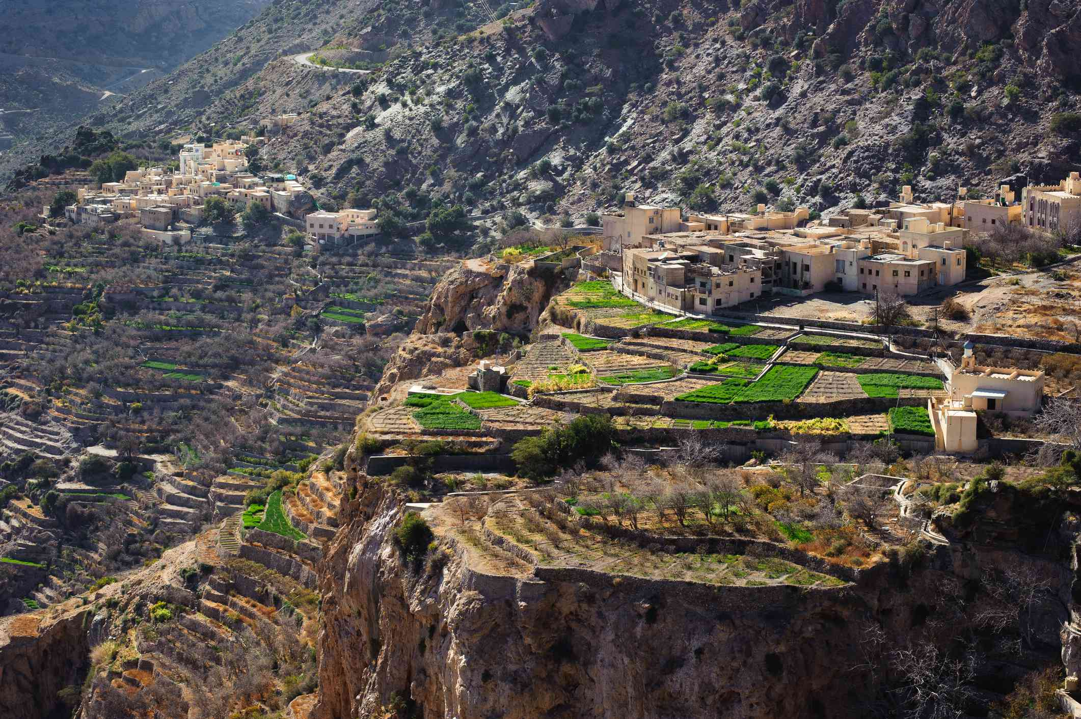 Agricultural terraces and villages precariously perched on the side of a cliff in the Jebel Akhdar region of the Hajar Mountains near Nizwa, Oman