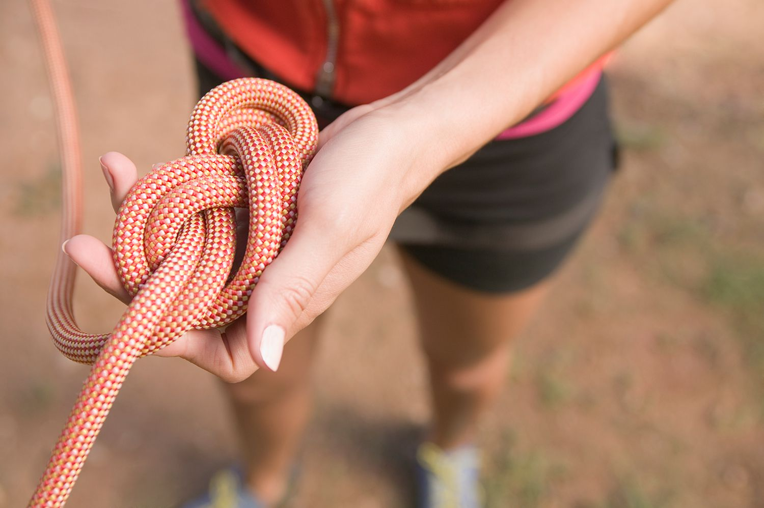 Person holding rope with knot.