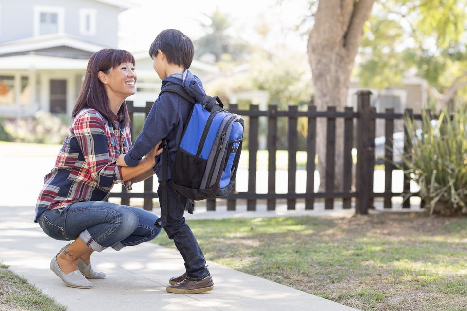 Mother saying goodbye to school boy son with backpack in front yard