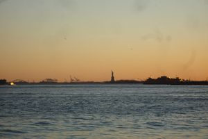 View of the Statue of Liberty at dusk from Brooklyn Bridge Park