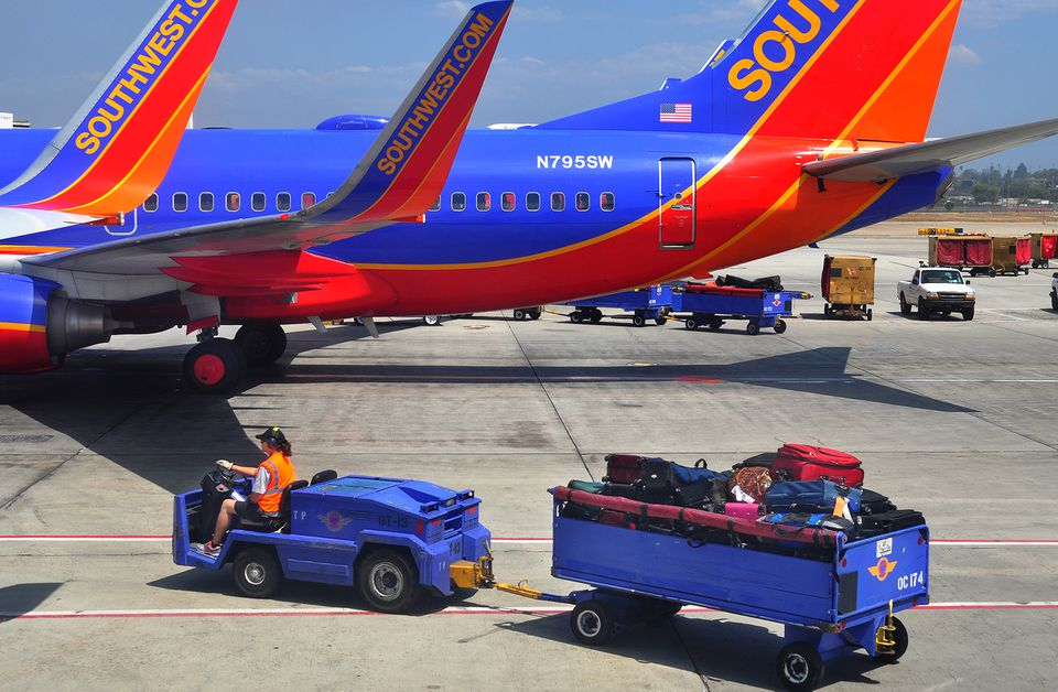 A Southwest Airlines baggage handler transports a cart of baggage