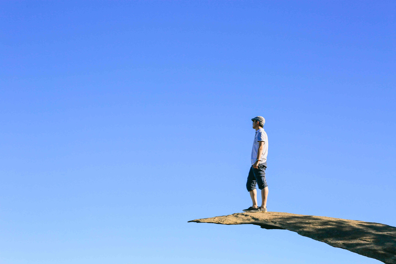 Man standing on Potato Chip Rock against blue sky, Mt. Woodson Summit, California