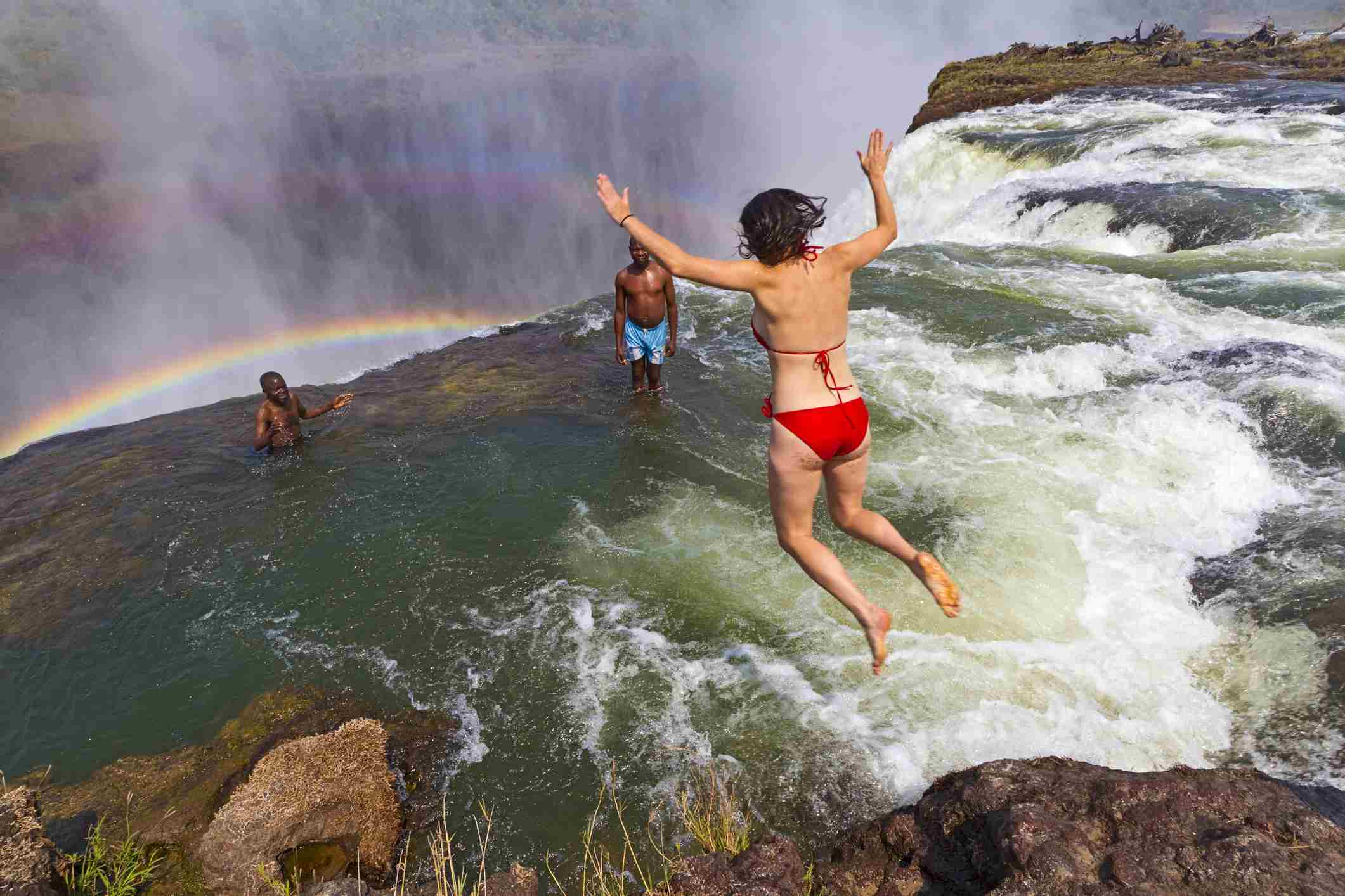 Woman jumping into Devil's Pool in Zambia