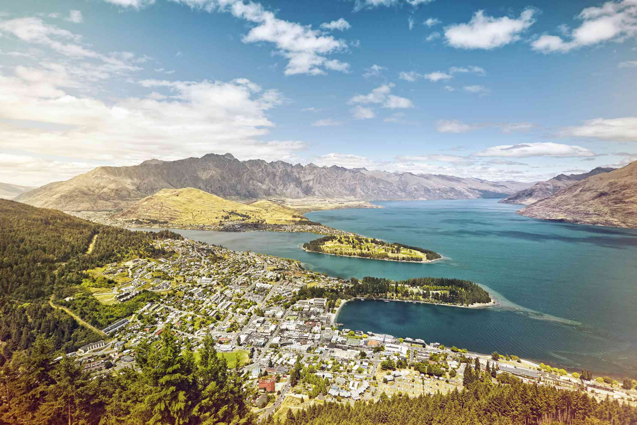 aerial view of Queenstown on the shores of blue Lake Wakatipu with mountains in background