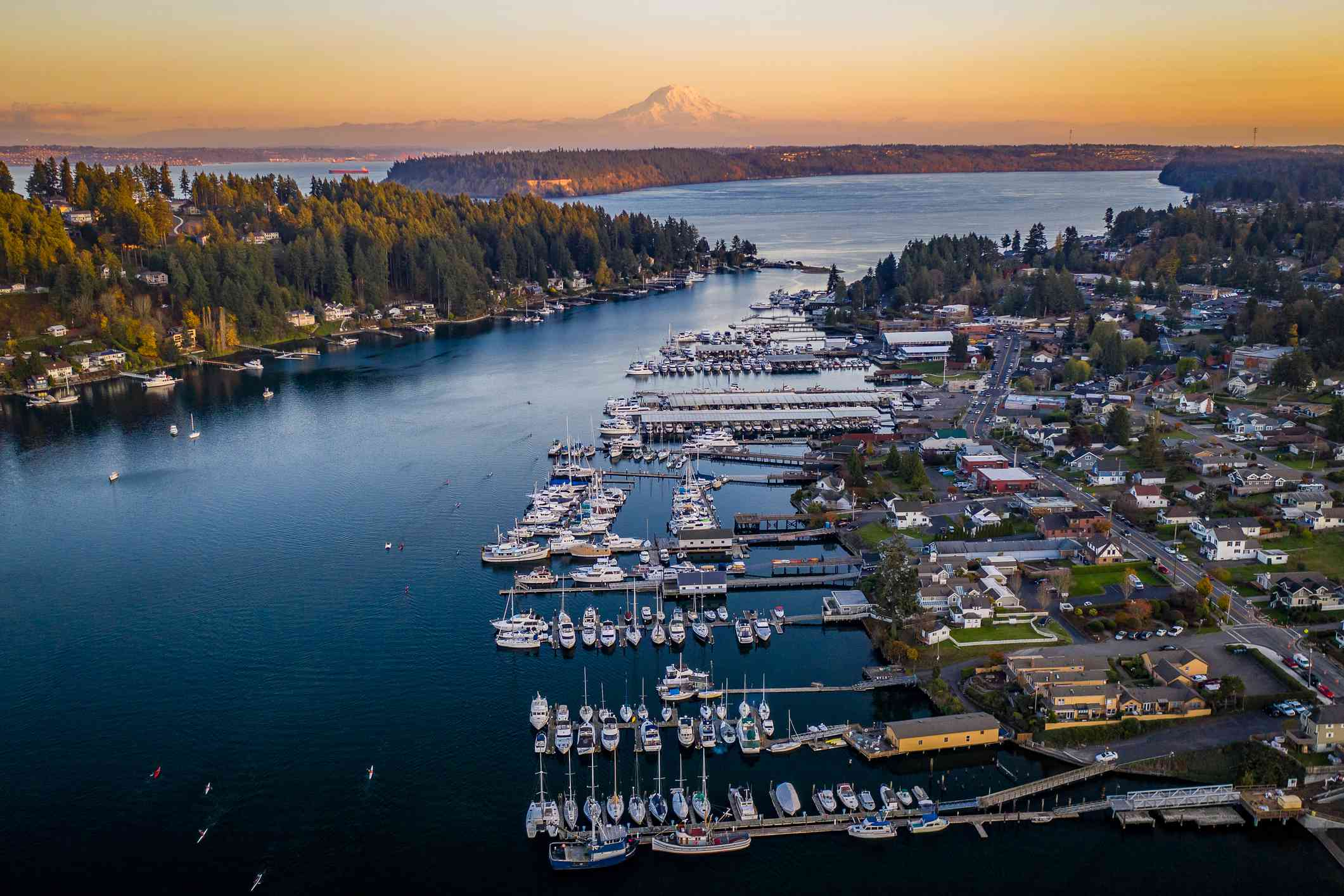 A drone view of boats in Gig Harbor Washington at sunset with Mt Rainier in the far distance
