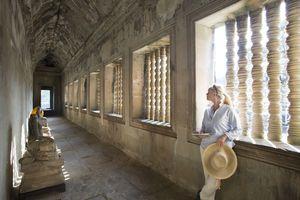 Woman pauses in Angkor Wat hallway, Cambodia