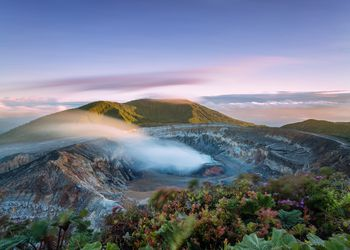 A view of a massive volcanic crater with clouds moving over it.
