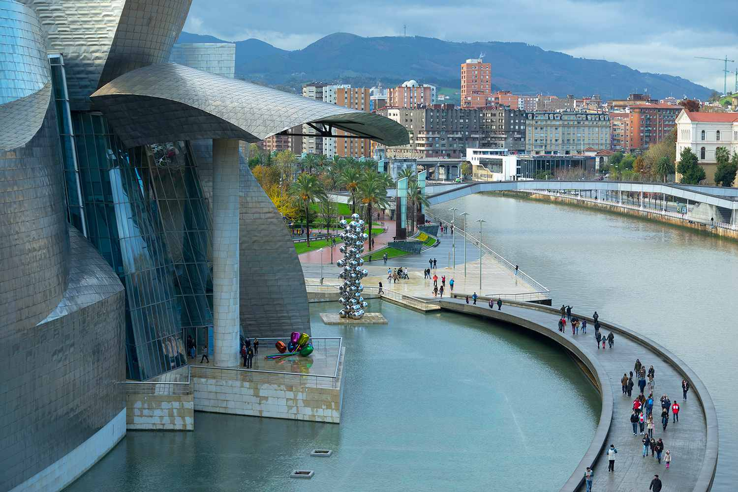 Aerial view of tourists on walkway over urban canal, Bilbao, Biscay, Spain
