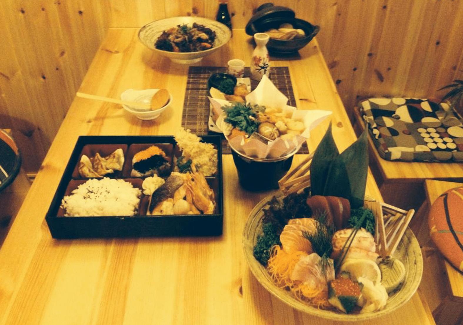platters of japanese food on light wood table