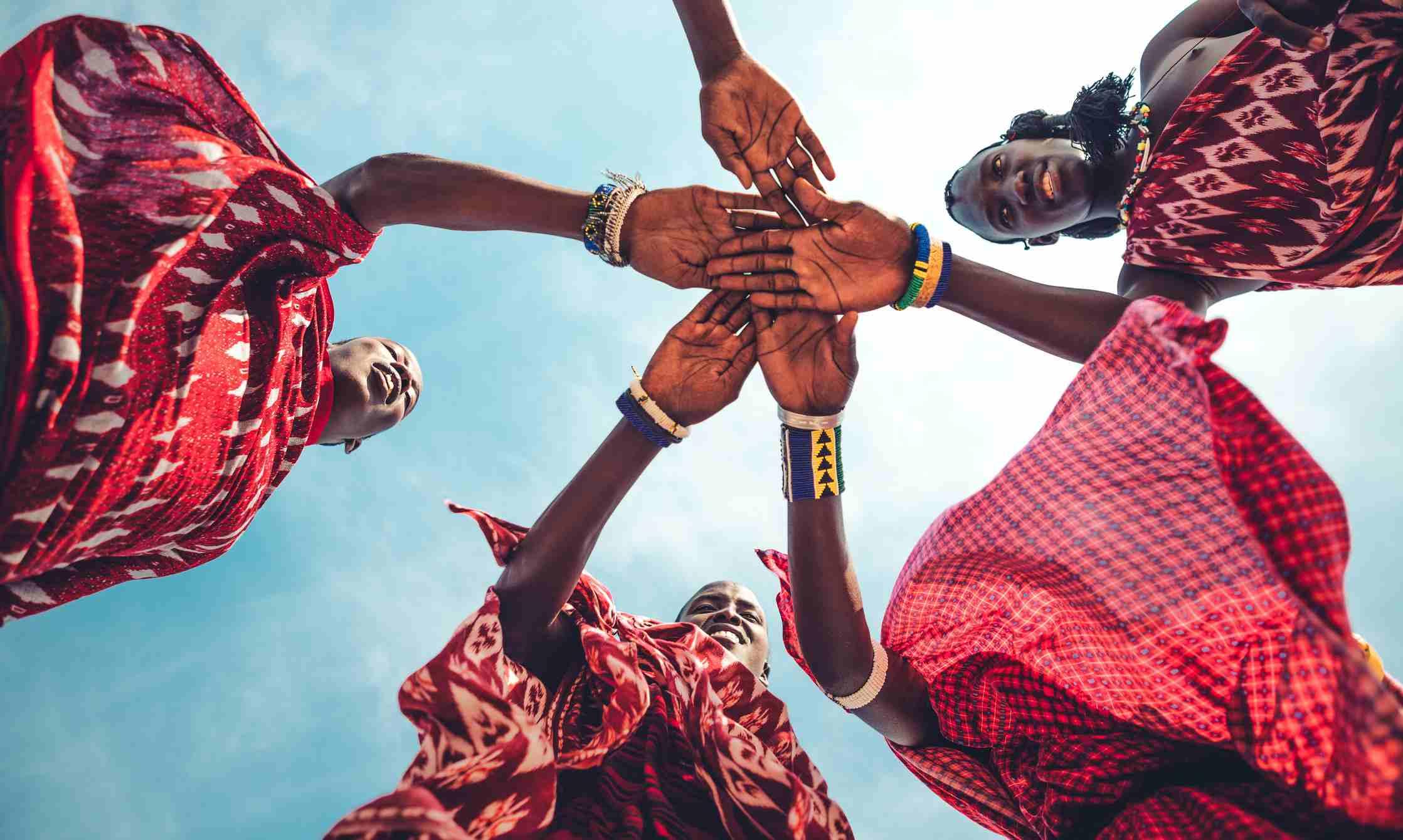 Masai in traditional clothes joining hands in unity (Zanzibar, Tanzania)