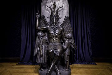 Dark bronze sculpture of a seated Baphomet (a goat-headed deity) with two bronze children looking up at Baphoment