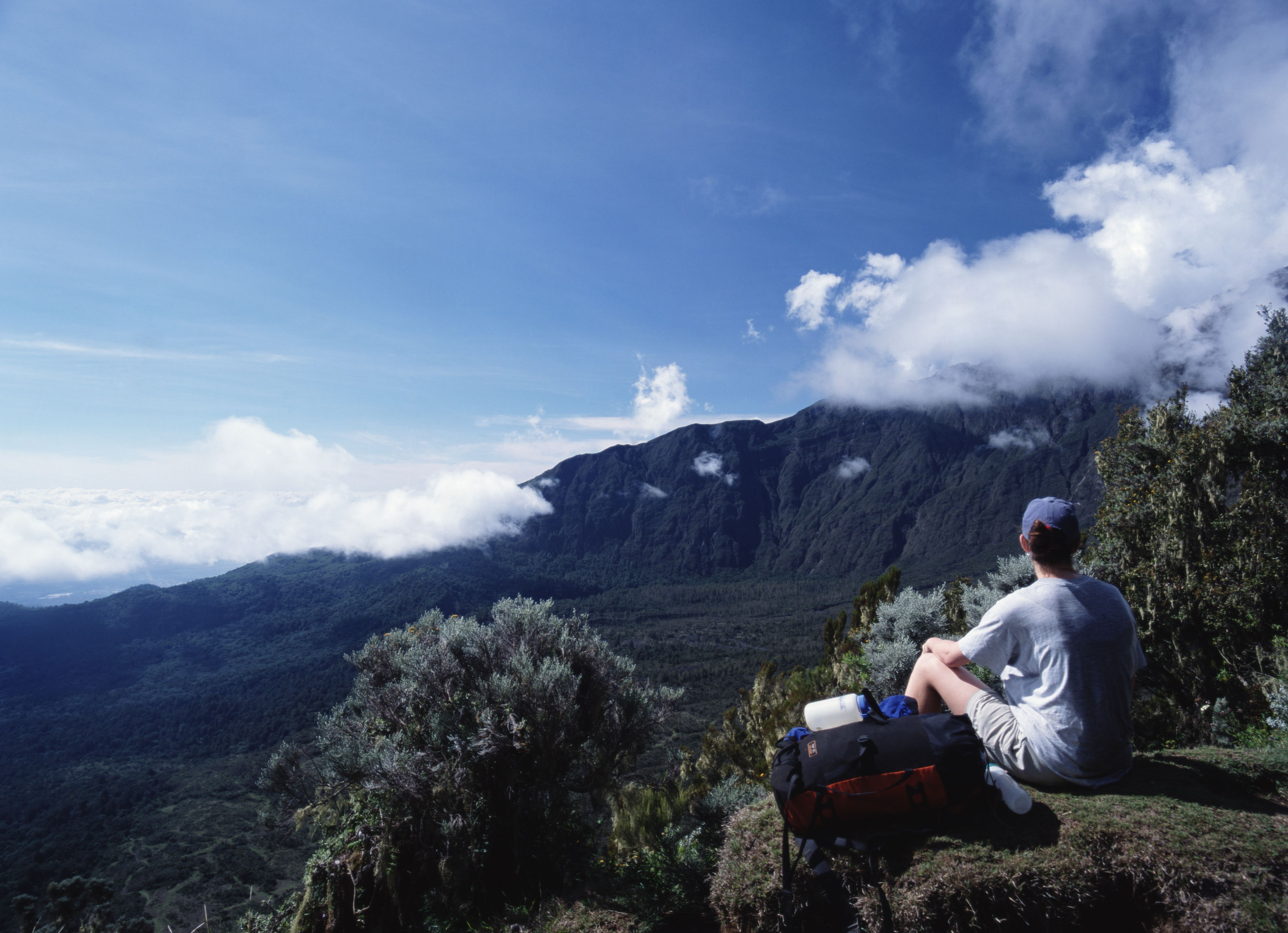 Woman with backpack sitting on edge of mountaintop