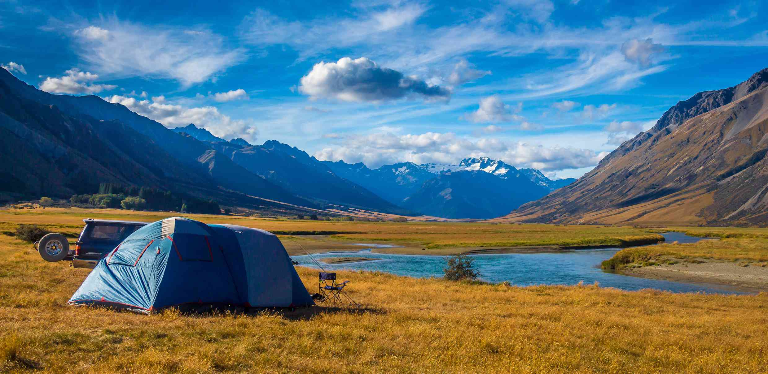blue tent in golden grassland with river and mountains in background