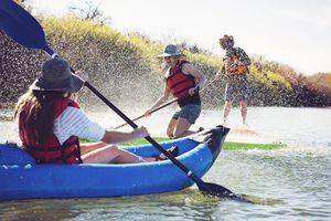 Friends splashing water on woman sitting in inflatable kayak while paddleboarding at lake