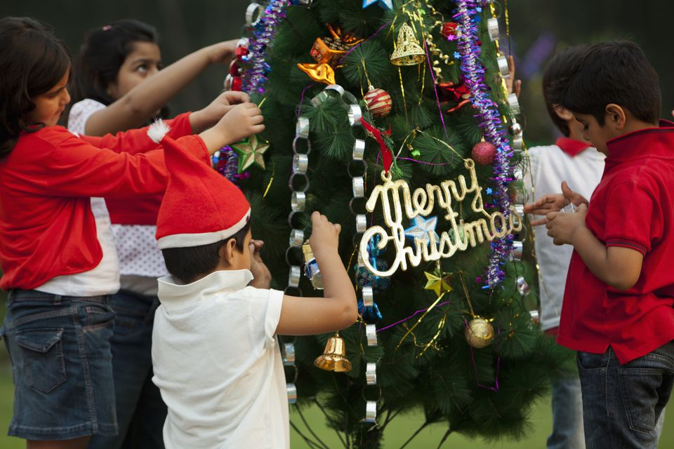 children decorating christmas tree in india