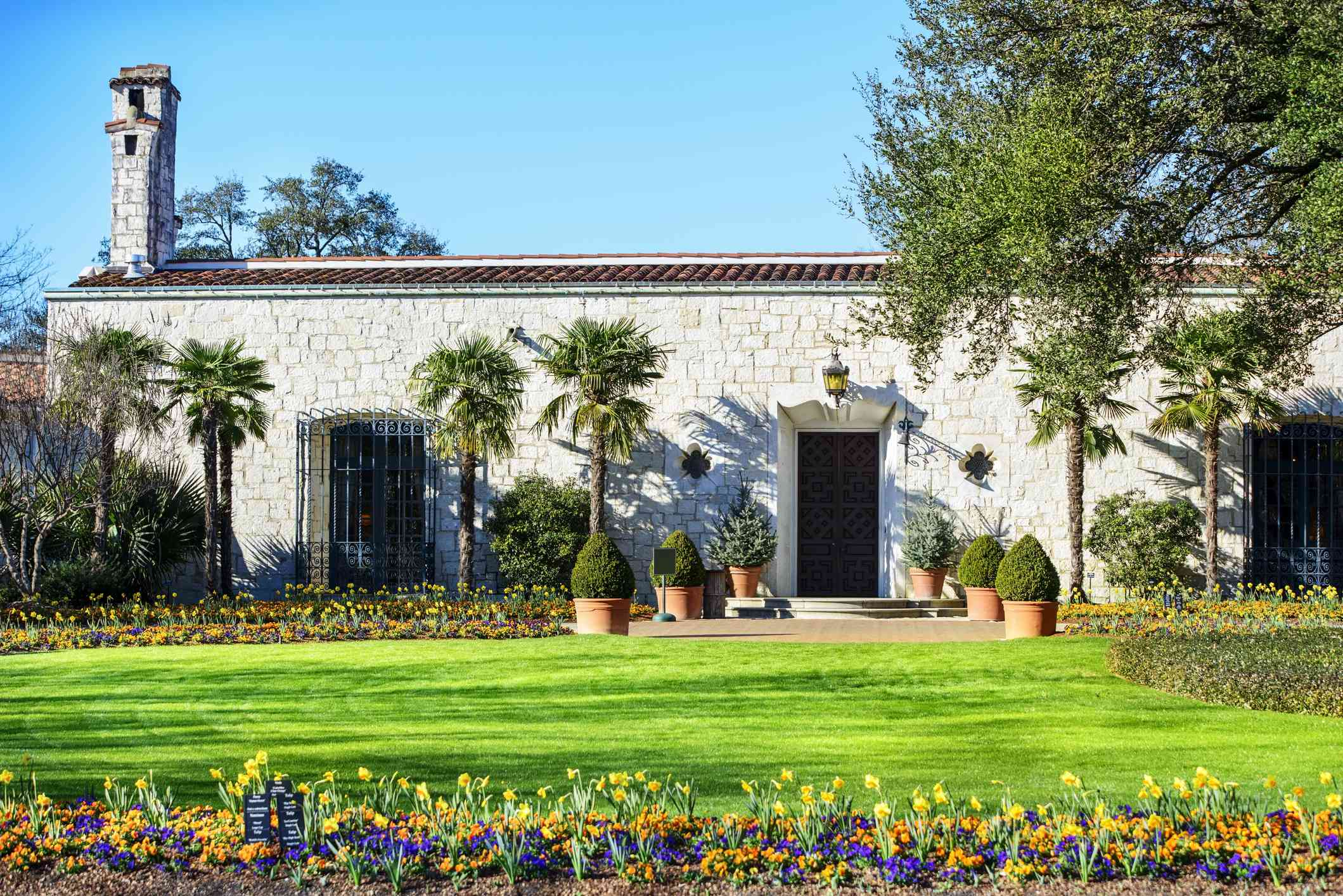 Stone building with palm trees and colorful flowers in front of it, Dallas Arboretum and Botanical Garden. Located in Dallas, Texas, USA.