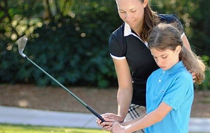 woman teaching child how to golf at Palmetto Dunes Oceanfront Resort: Hilton Head, SC
