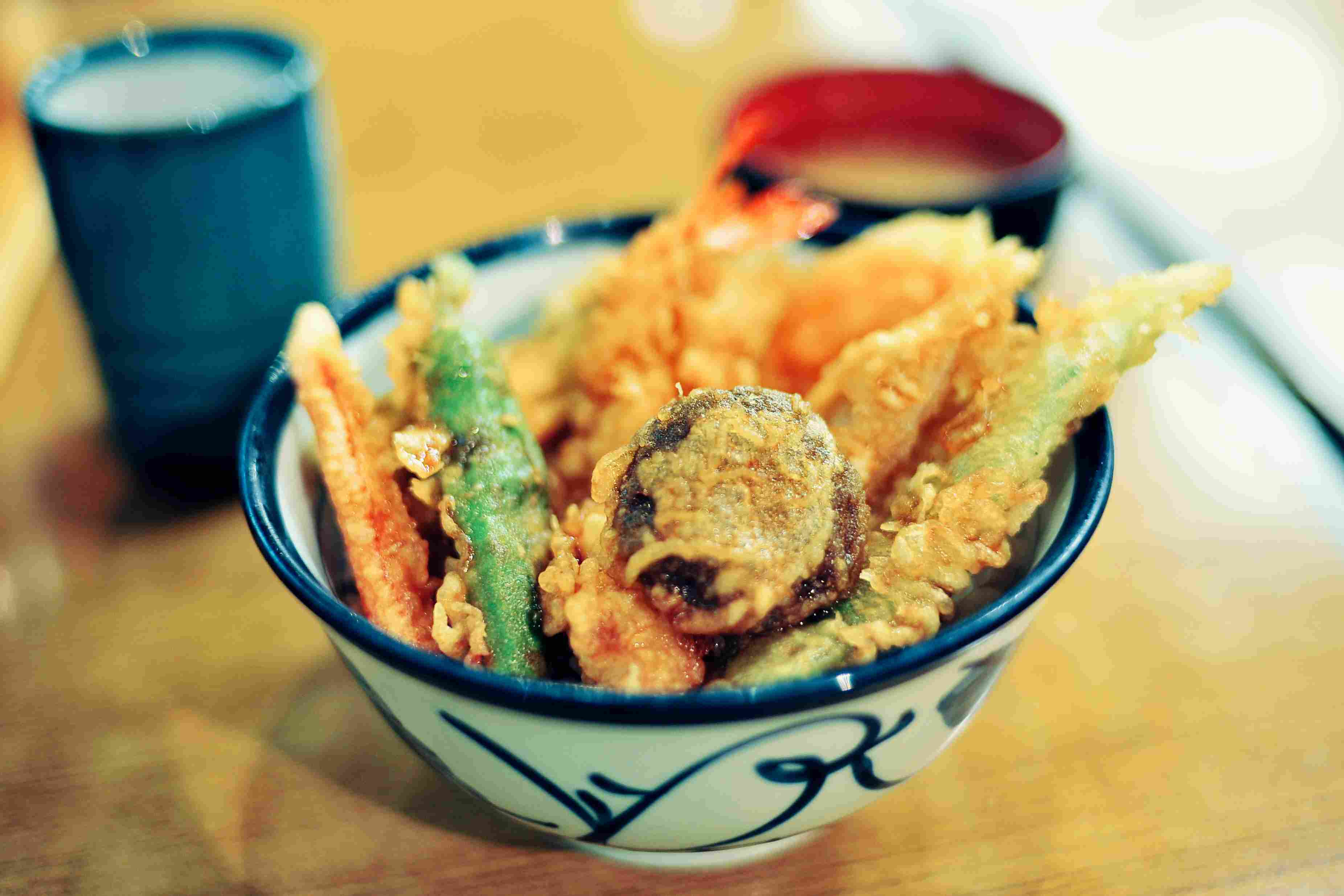 Big bowl of mixed vegetable and shrimp tempura on rice, known as 'tendon' in Japanese.