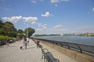 People walking and sitting in waterside park