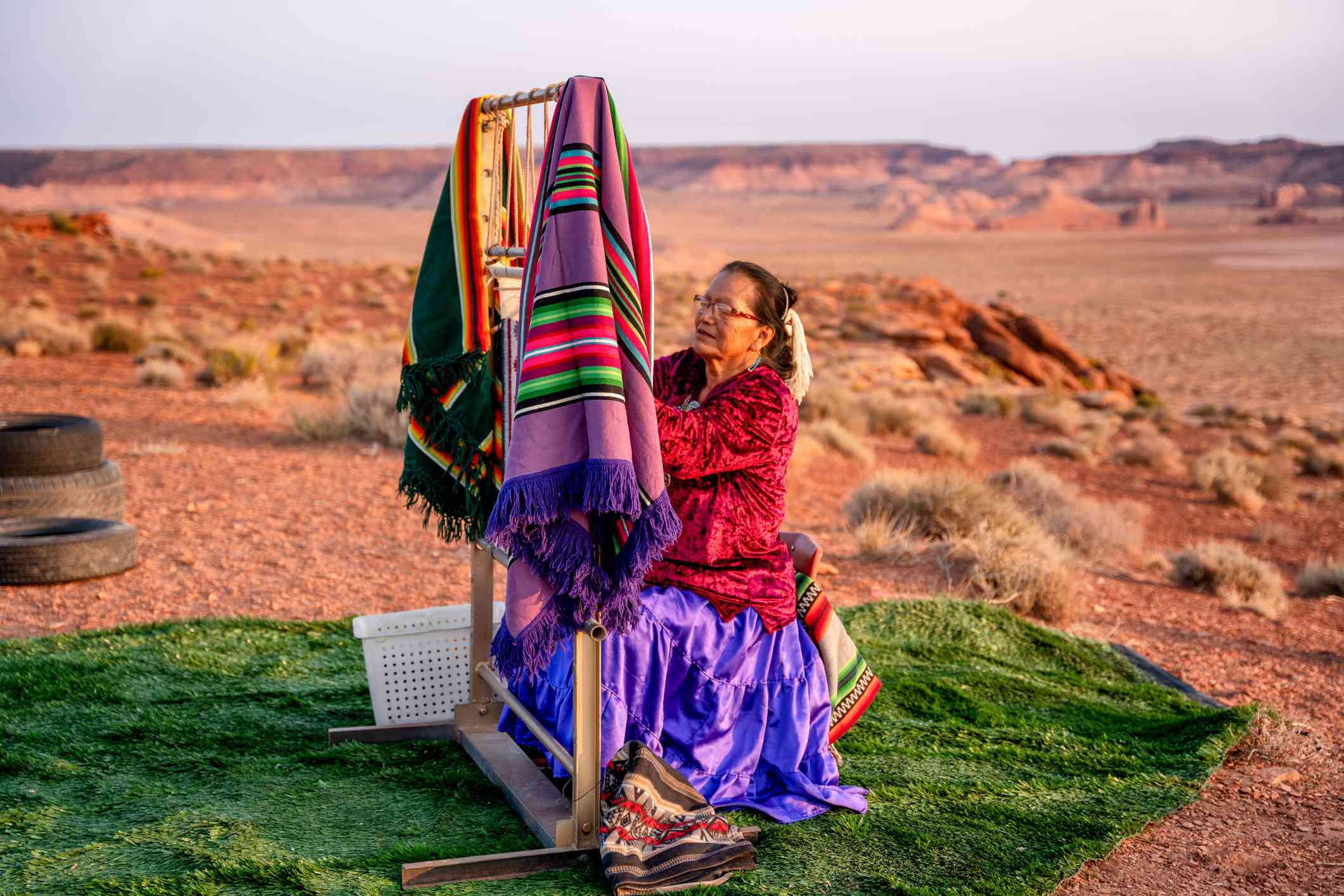 Elderly Navajo Woman Weaving a Traditional Blanket or Rug on a Loom in the Arizona Desert at Dusk