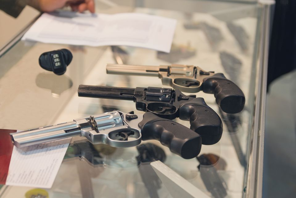 Handguns on a counter in a shop.