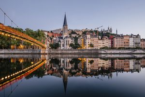 Paul-Couturier Footbridge over Saone river against buildings in city during sunset