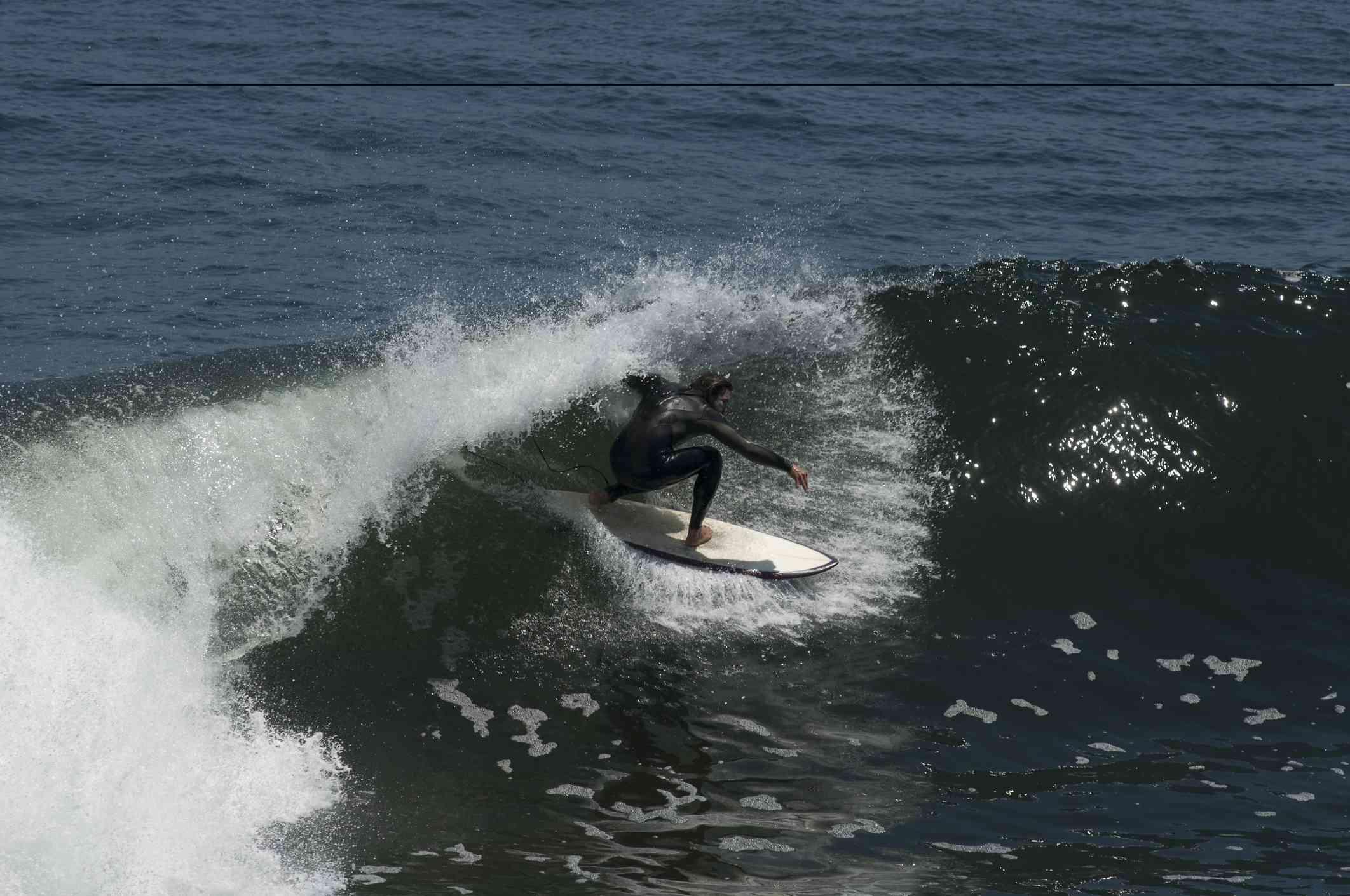 A man wearing a wetsuit surfing Punta de Lobos, Pichilemu, Chile
