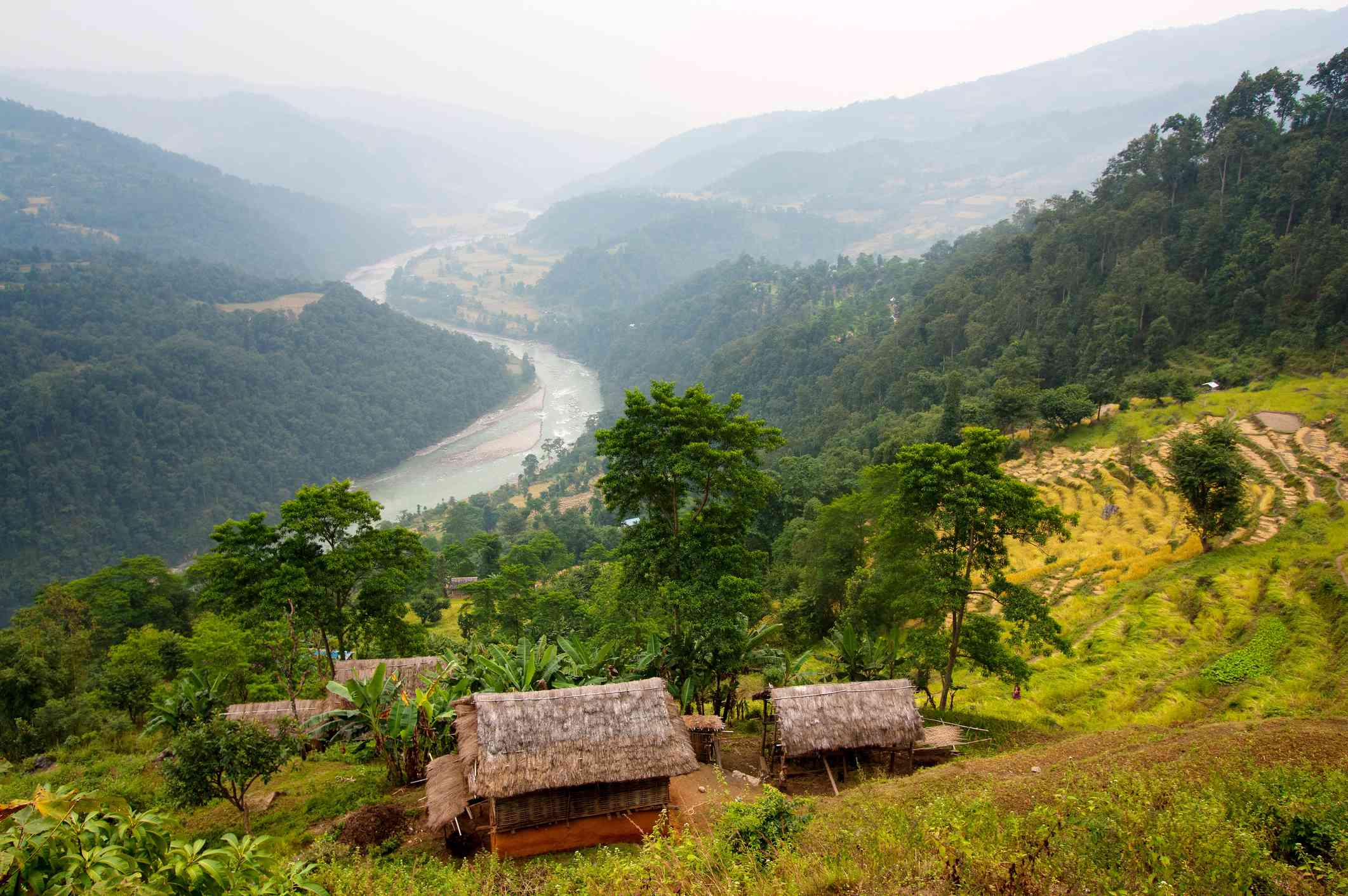 grass-roofed huts on terraced hillside farmland with river running through a valley in background