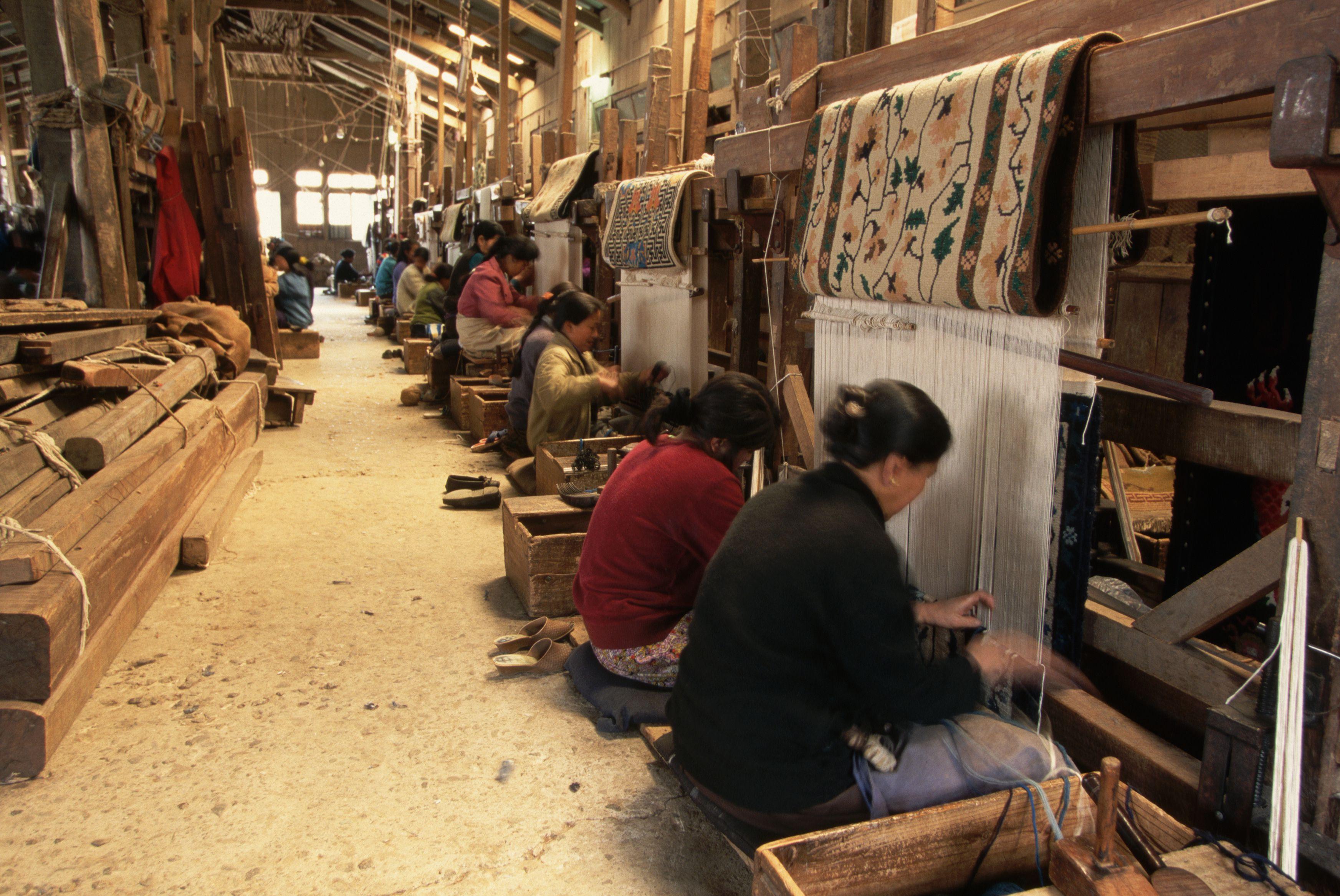 Tibetan women weave carpets on looms at a Tibetan refugee camp in Darjeeling.