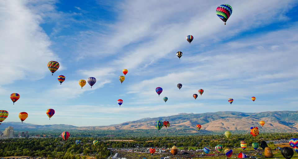 Panoramic view of many colorful hot air balloons taking flight