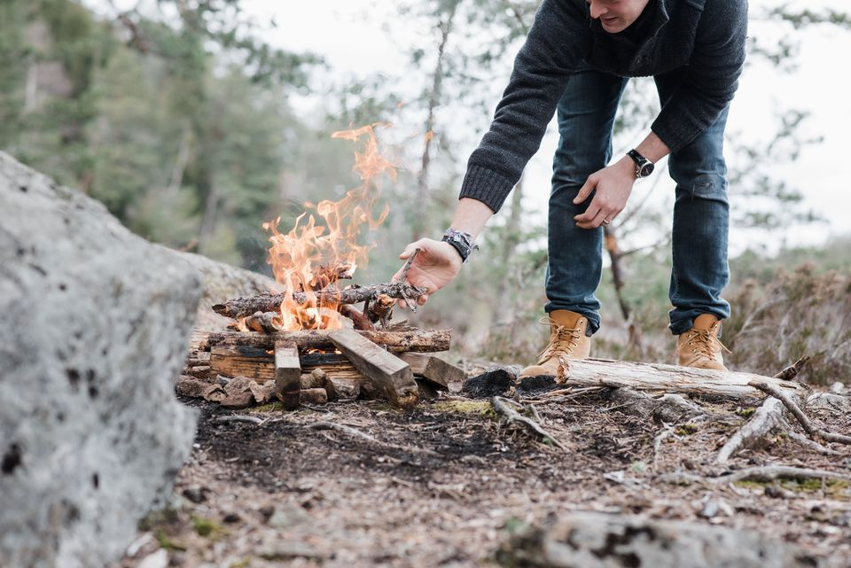 Man stacking firewood to build a campfire