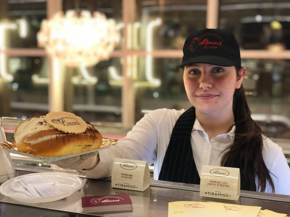 Pasticceria Linari employee handing over a large pastry