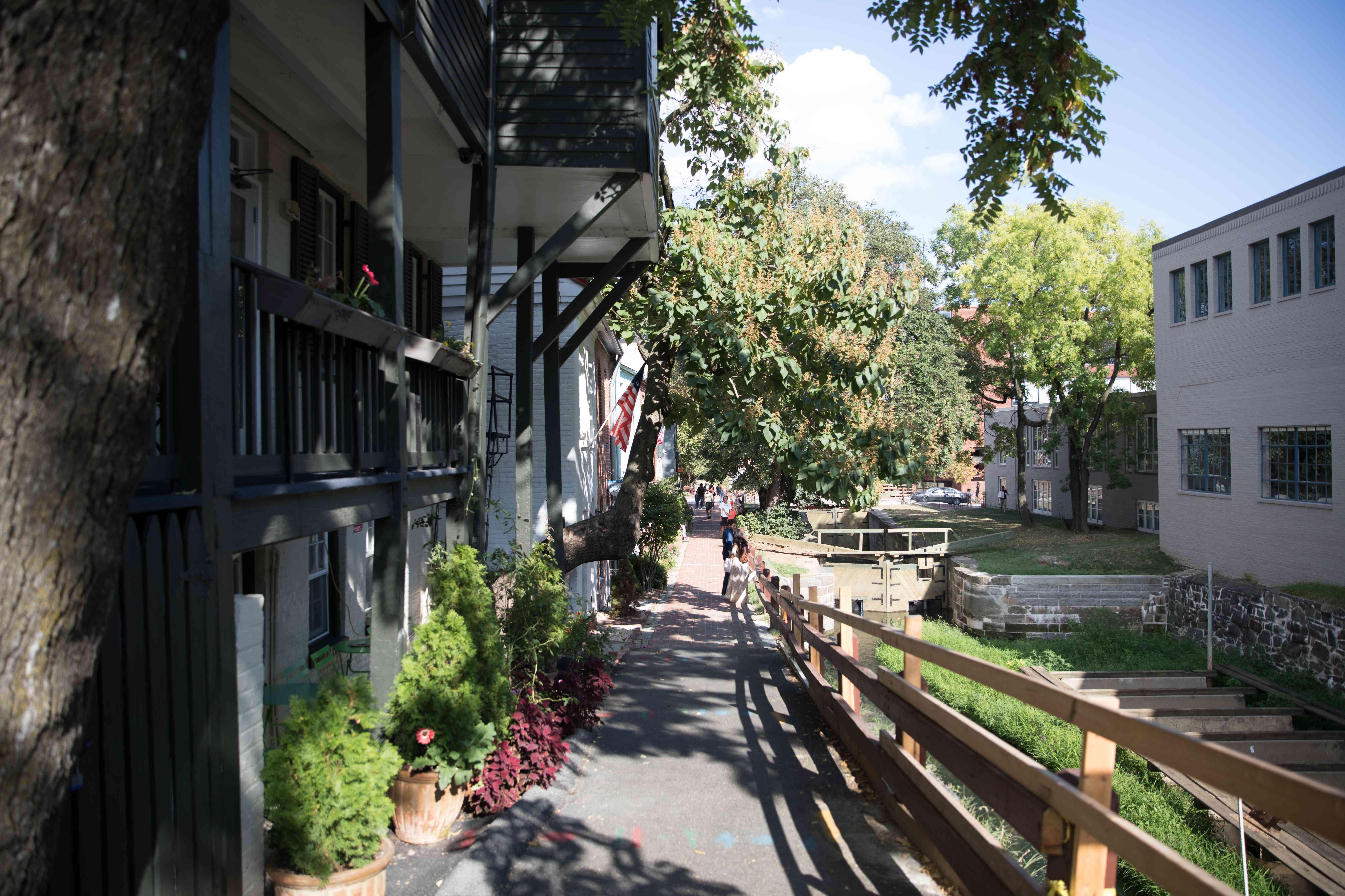 People walking along the sidewalk by historic houses in Georgetown