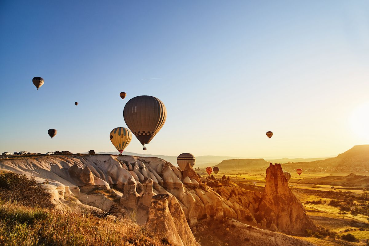 Hot air balloons rise above a rocky landscape at dawn