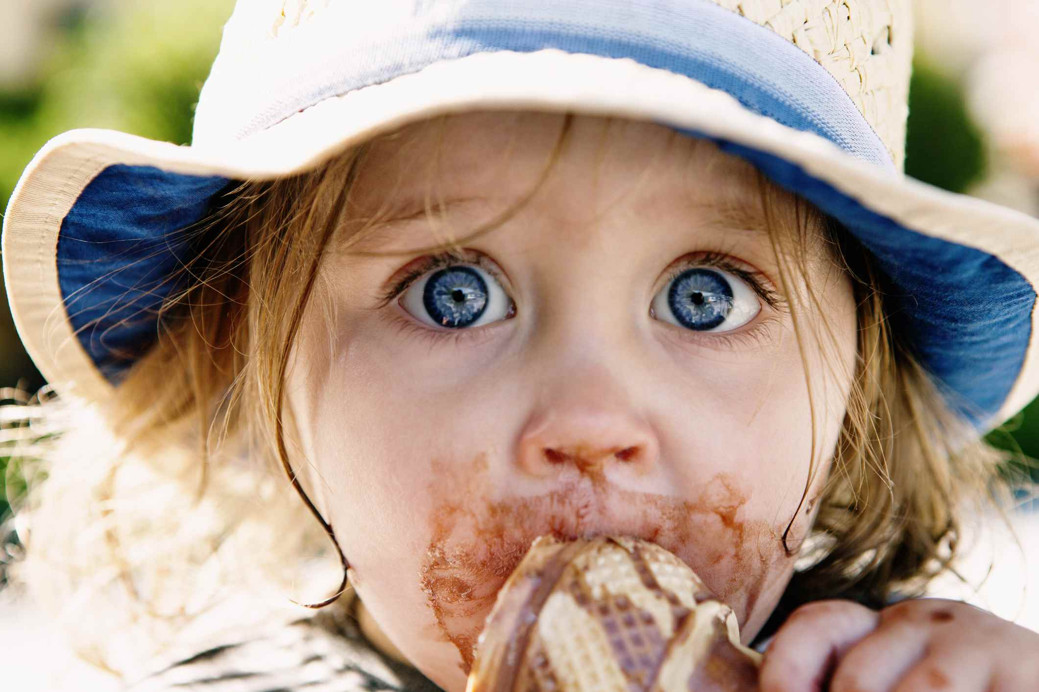 Ice cream heaven - child with big blue eyes messily eating ice cream