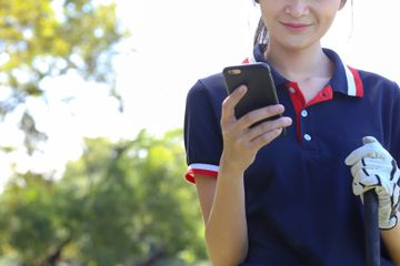 Smiling Young Golfer Using Smart Phone While Standing At Park