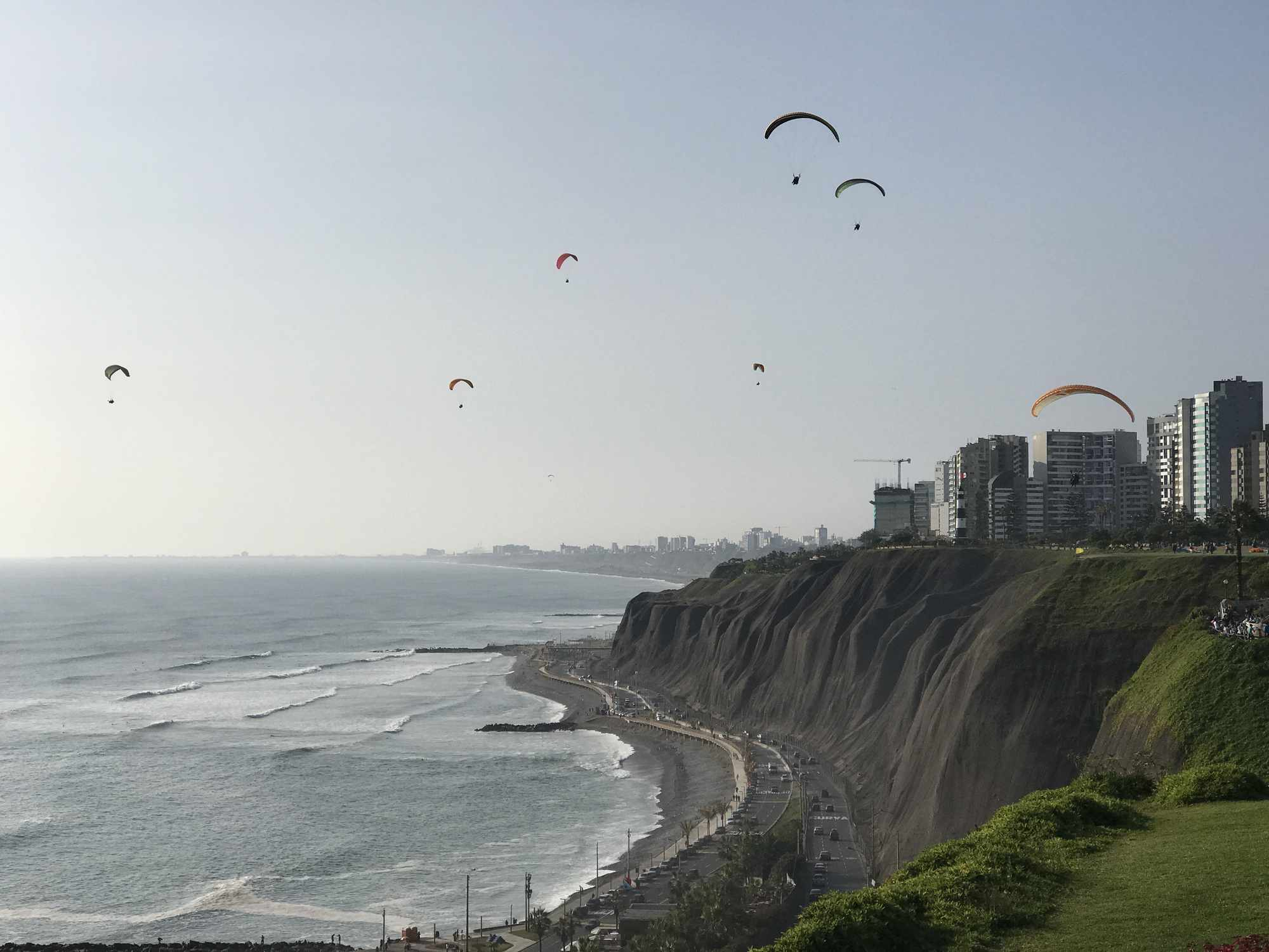cliffs with sea below and paragliders in the sky