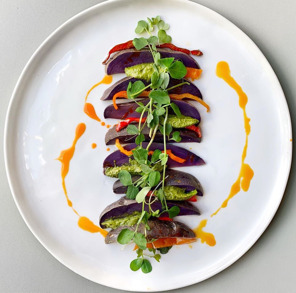 purple potato wedges on a white plate garnish with sprouts and an orange sauce